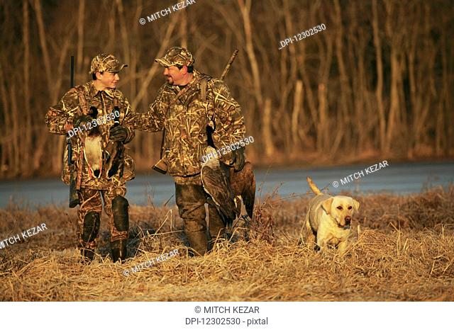 Father And Son Hunters Carrying Decoys And Birds