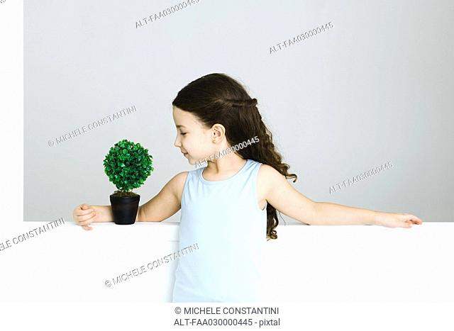 Little girl standing with arm around potted plant