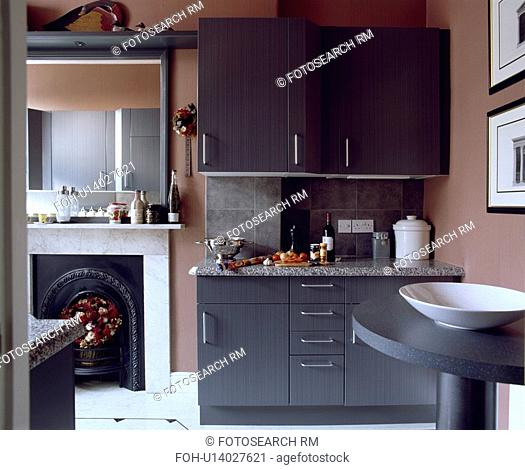 Modern pale brown kitchen with grey fitted cupboard beside open door to livingroom