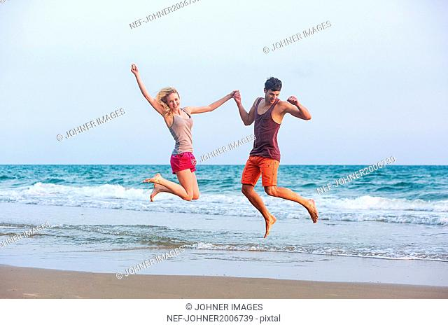 Young couple jumping on beach