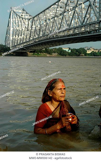 A local Marwari lady is paying her homage to Sun God, early in the morning at Jagannath ghat India August 5, 2005