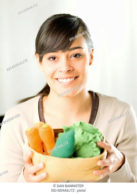 Young woman holding fresh vegetables, portrait
