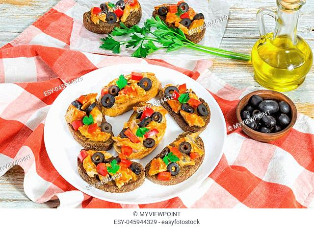 Crostini with pieces of mackerel fish, rings of black olives, red bell pepper on white plate on kitchen cloth, view from above
