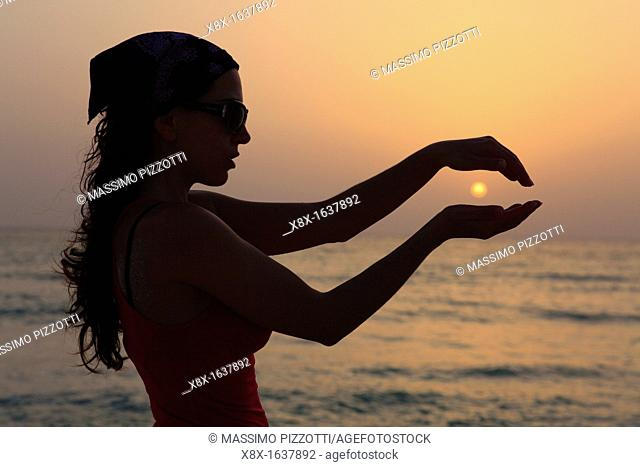 Sihouette of a woman holding the sun
