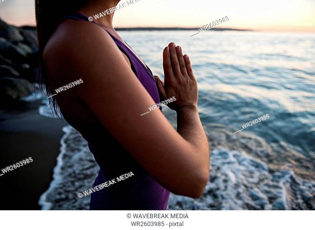 Mid section of woman meditating on beach