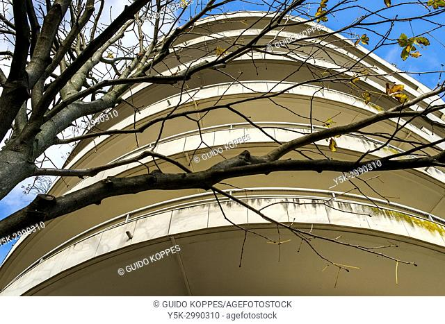 Paris, France. Front facade of a La Defense situated Apartment Building on a street corner, with a tree in front during fall season