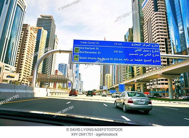 City of Dubai. Road signs driving along city centre Sheikh Zayed Road. Al Yaquob Tower in distance. United Arab Emirates