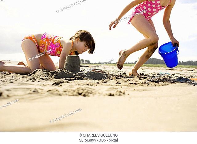 Girls making sandcastles at beach