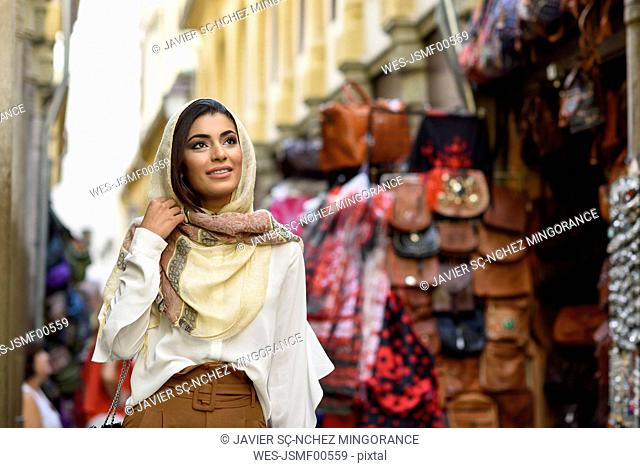 Spain, Granada, young muslim tourist woman wearing hijab during sightseeing in the city