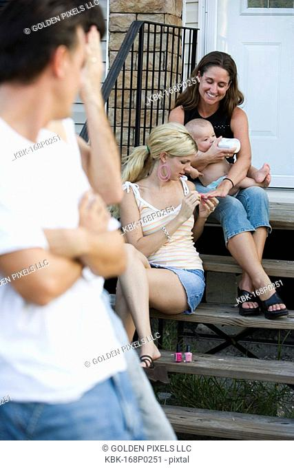 Family and friends relaxing on front steps of a home