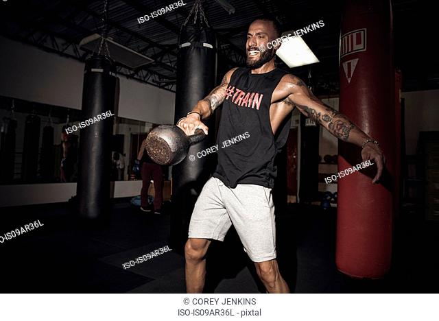 Male boxer lifting kettlebell with gritted teeth in gym