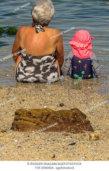 Granny. A grandmother and her little grand daughter sit in the sand at the edge of a tidal pool. Cape Town, South Africa
