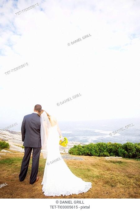 Rear view of married couple standing by sea