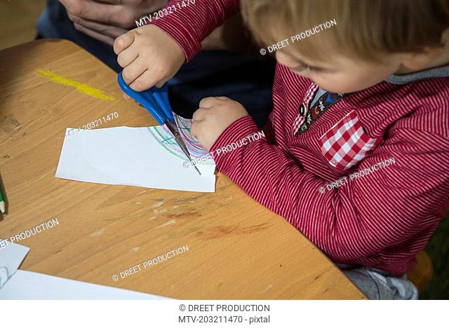 Close up of a little boy cutting a paper with scissor, Munich, Germany