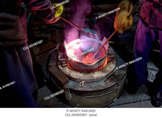 Workers stirring molten aluminium alloy in precision casting factory