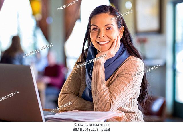Hispanic woman using laptop in cafe