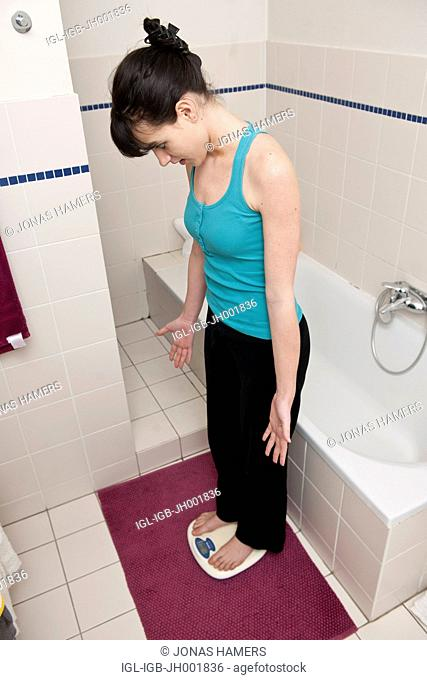 This picture shows a young caucasian woman with brown hair as she stands on her balance and checking her weight