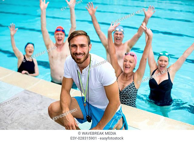 Instructor with carefree senior swimmers in pool