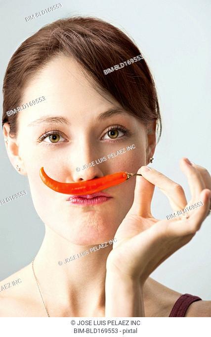Caucasian woman smelling chili pepper