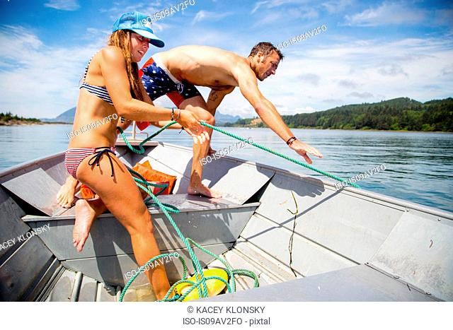 Young woman and mid adult man hauling in rope on fishing boat, Nehalem Bay, Oregon, USA
