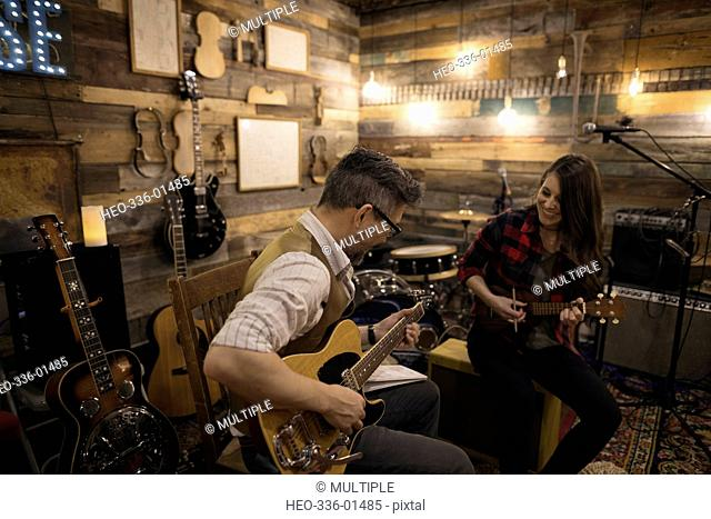 Singer-songwriter musicians playing guitar and ukulele, writing music on stage