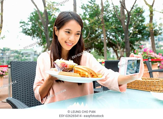 Woman taking photo with her waffle in restaurant