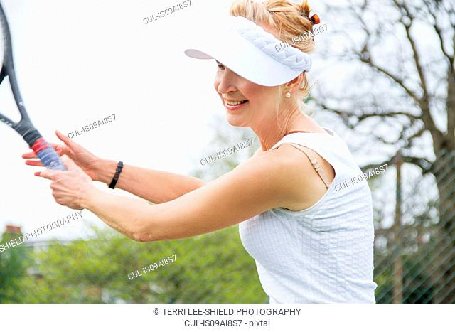 Mature female tennis player playing tennis