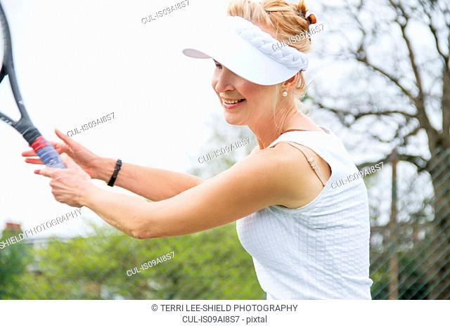 Mature female tennis player playing tennis