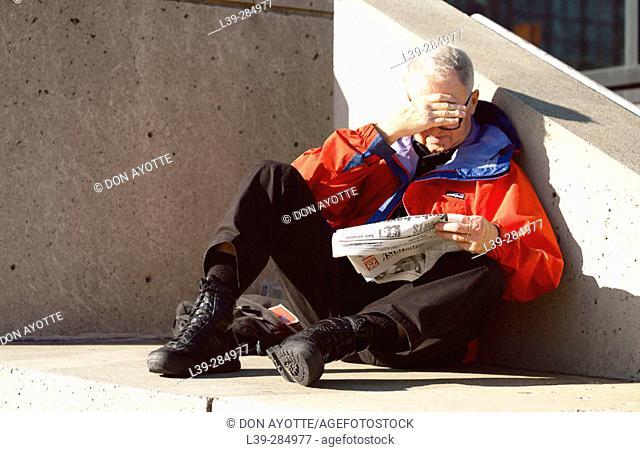 Man reading newspaper outside Javits Center. New York City, USA