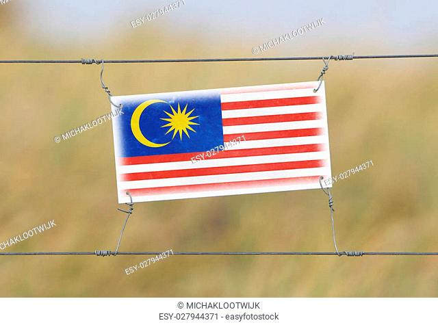 Border fence - Old plastic sign with a flag - Malaysia