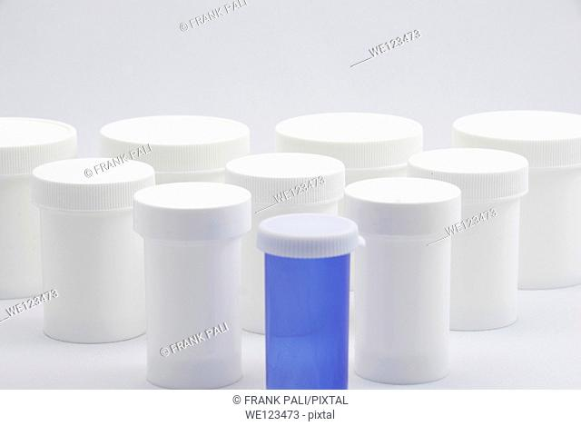 Ten white bottles of different sizes and one white on a white background