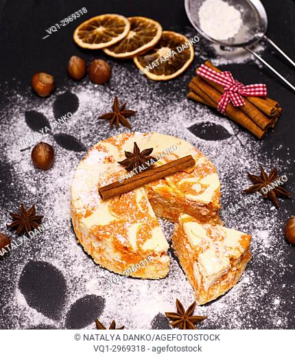 pie from cottage cheese and pumpkin on a black background, top view