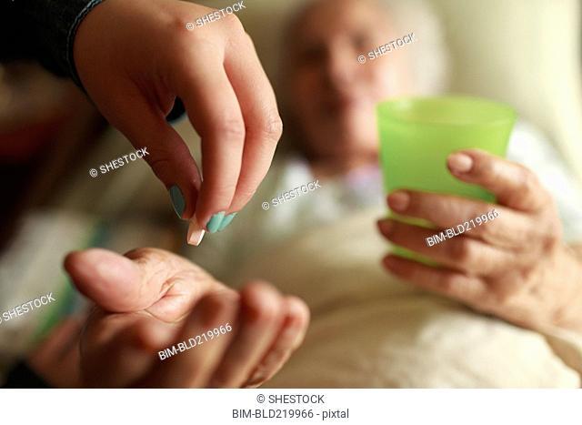 Granddaughter giving grandmother medication in bed