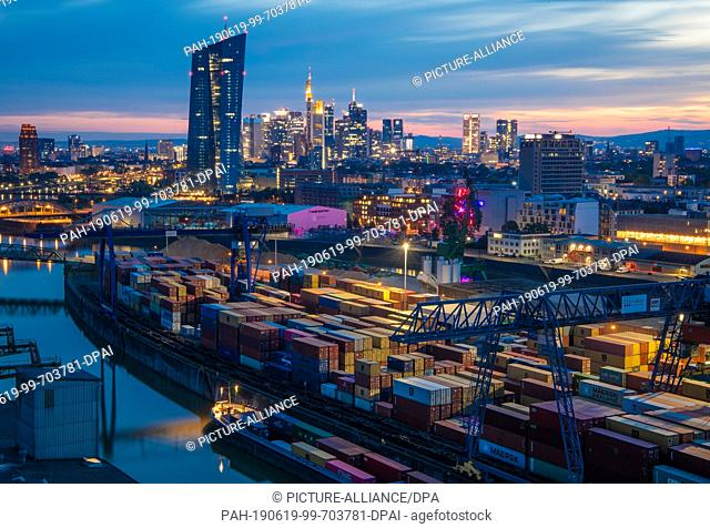 18 June 2019, Hessen, Frankfurt/Main: While in the background the lights of the bank towers behind the ECB shine in the last light of the day