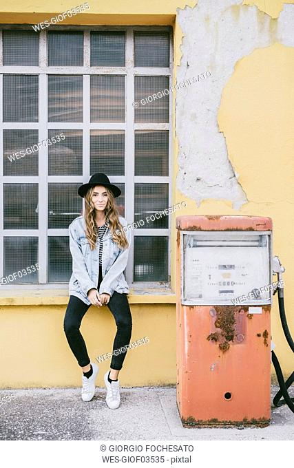 Fashionable young woman wearing hat sitting on window sill beside an old petrol pump