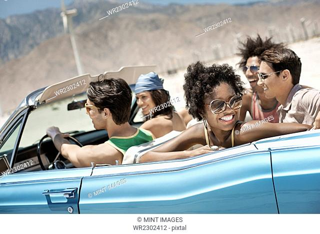 A group of friends in a pale blue convertible on the open road, driving across a dry flat plain surrounded by mountains