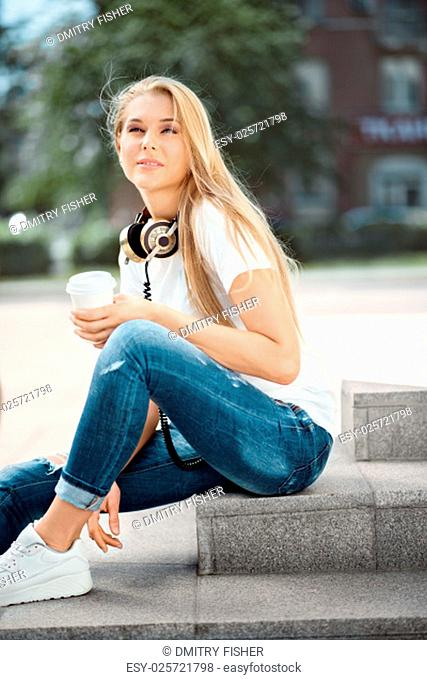 Happy young woman wearing vintage music headphones around her neck and sitting on stairs with a take away coffee cup against urban city background