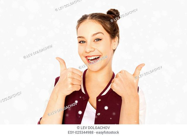 winter, christmas, people, gecture and teens concept - happy smiling pretty teenage girl showing thumbs up over gray background and snow