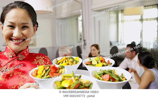 Smiling waitress presenting tray with bowls of vegetables at a chinese restaurant