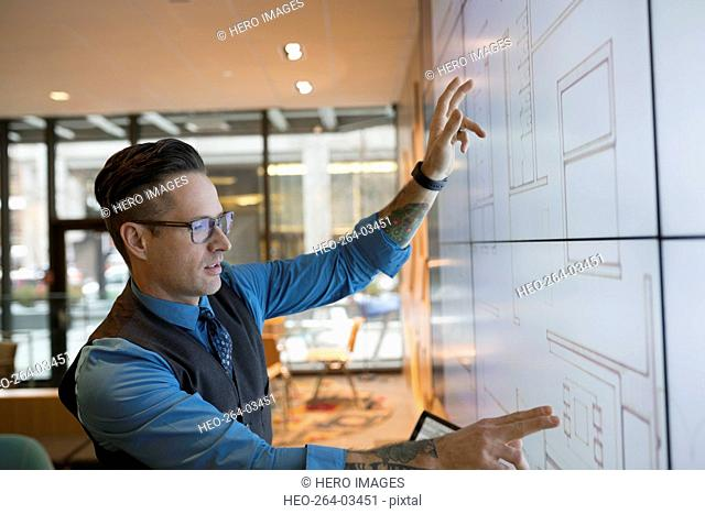 Architect using projection screen in conference room