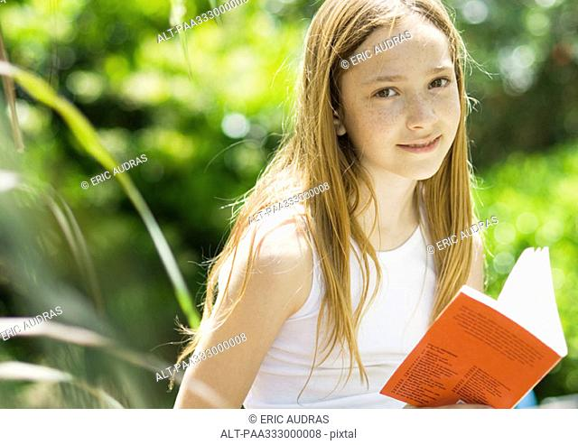 Girl with book, smiling at camera