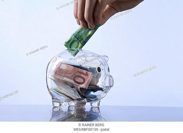 Man putting money into piggy bank