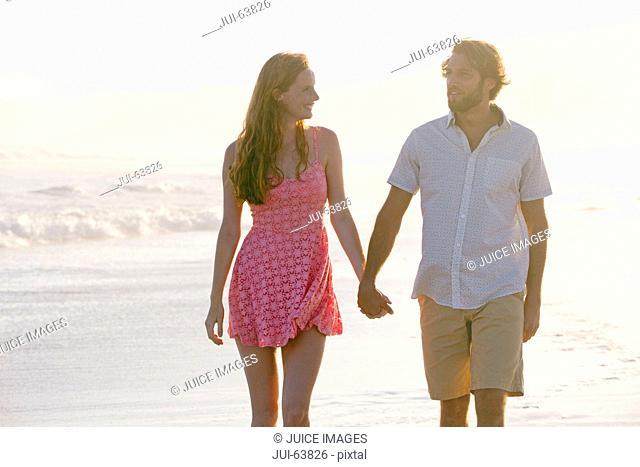 Couple, holding hands, walking along sunny beach