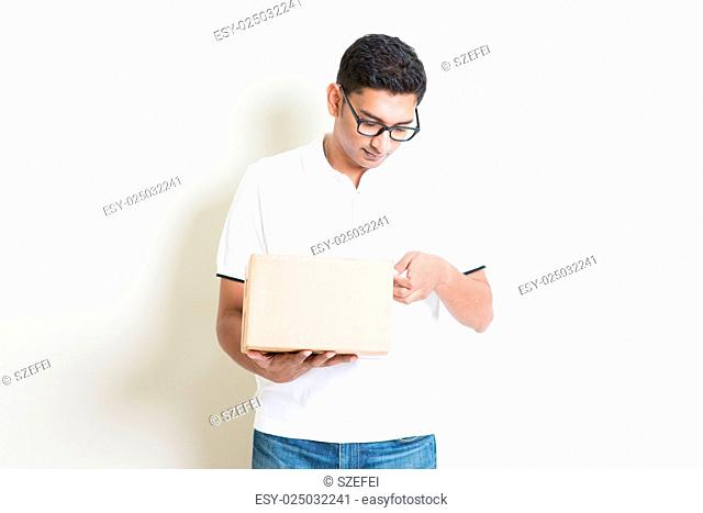 Indian man opening a brown box, standing on plain background with shadow. Courier delivery service concept. Asian handsome guy model
