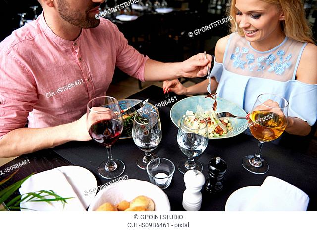 Man taking trying food girlfriend's lunch at restaurant table