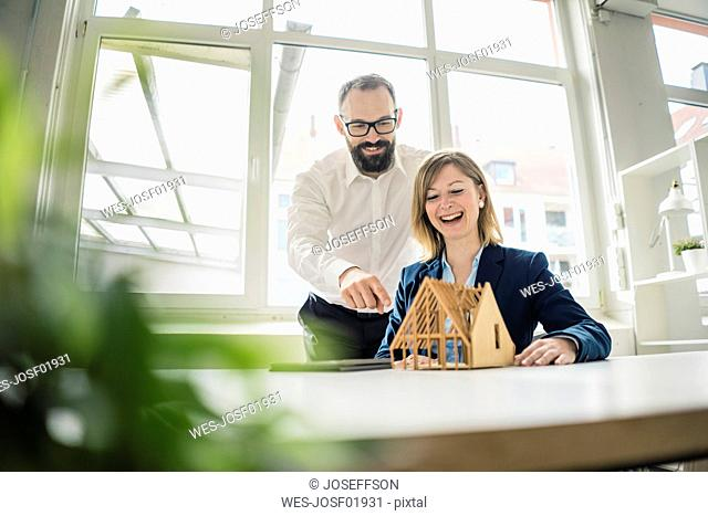 Laughing woman and man with house model in office