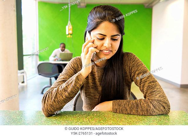 Aachen, Germany. Female Indian exchange student having a mobile phone conversation via an internet app with her mother in India