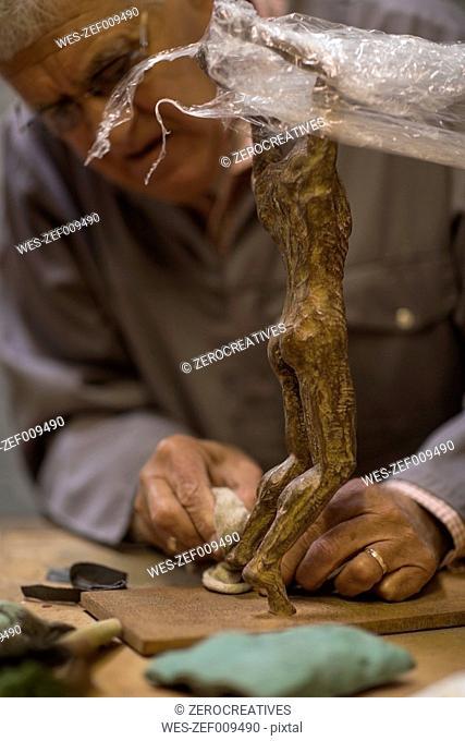 Senior man working on bronze figurine