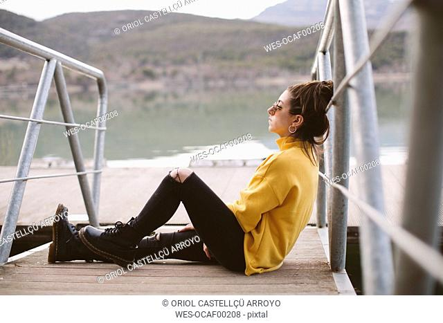 Pensive young woman relaxing on jetty