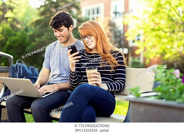 A young man and young woman sit together on a bench on the university campus using a laptop and checking social media on a smart phone while drinking coffee;...